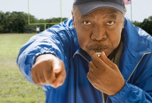 A coach pointing and blowing his whistle.