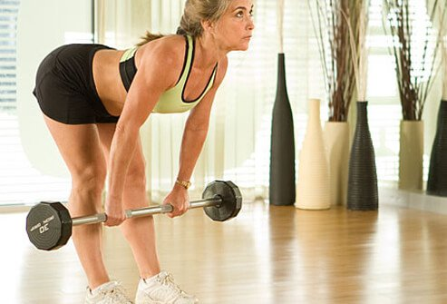 To do a deadlift holding a bar or free weights, stand up straight with feet hip–width apart.