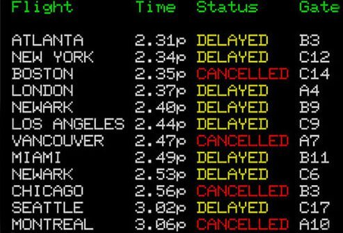 Airport sign displaying delayed and cancelled flights.