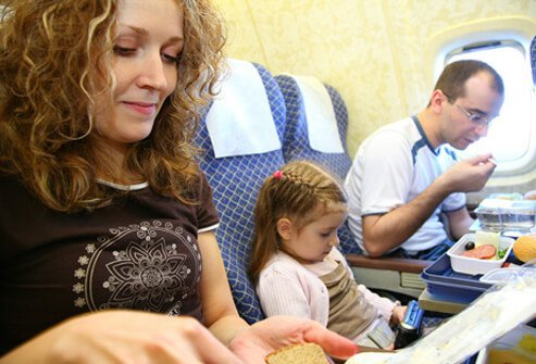 Child playing video games while parents eat on plane.