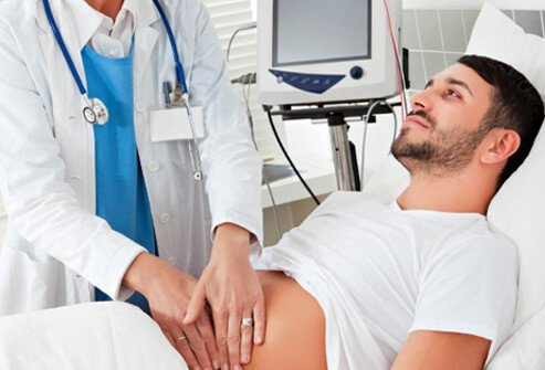 A doctor performs a physical examination on a male patient with abdominal pain.