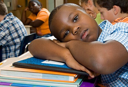 A boy daydreams in class while other students work.