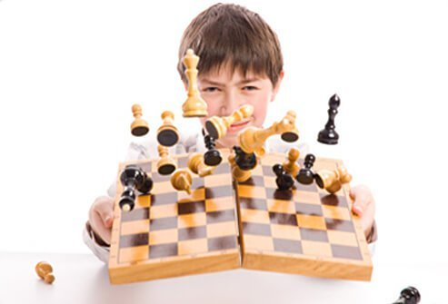 A boy intentionally ruins a game of chess by knocking pieces over.