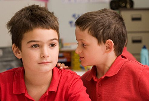 A boy interrupts another boy in a classroom.