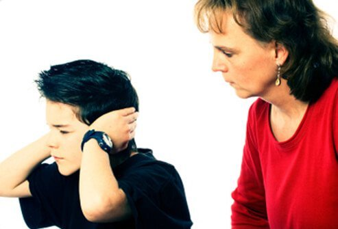 A boy covers his hears and does not listen to his mother.