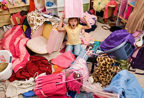 A girl sits in her disorganized and messy bedroom.