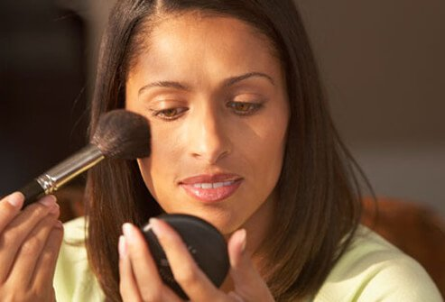 A woman applies makeup.