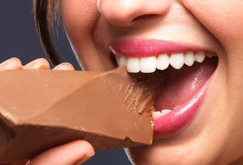 A woman eats chocolate.