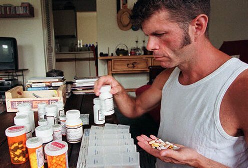 AIDS patient sorts through his daily medications.