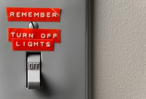 Light switch with a reminder note to turn off lights.