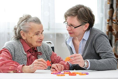 A caregiver helping a woman with Alzheimer's work on a puzzle.