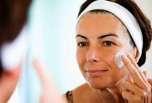 Photo of a woman moisturizing her face.