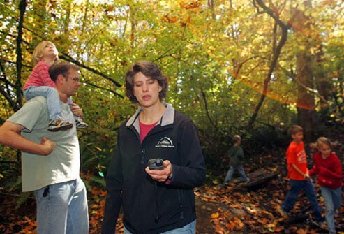 Photo of a woman geocaching with her family.