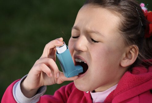 A young girl with allergic asthma uses her asthma inhaler.