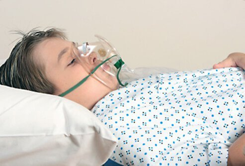 Boy laying in a hospital bed breathing with an oxygen mask.