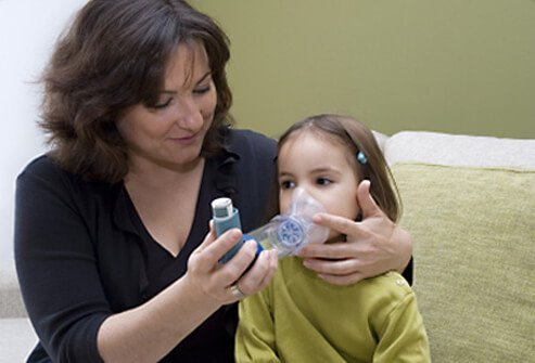 Mother helping daughter with her asthma inhaler.