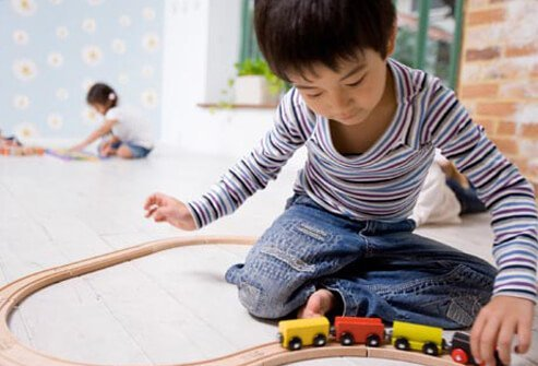 A boy with autism playing with a toy train.