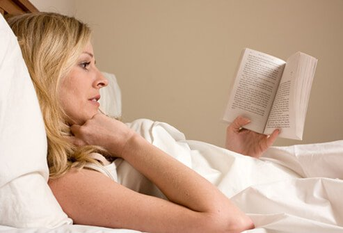 Woman reading a book in bed.