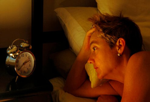 Woman that can't sleep staring at the clock.