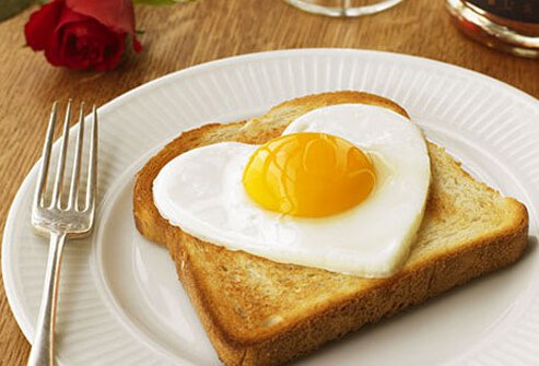 Photo of a heart shaped fried egg on a piece of toast.