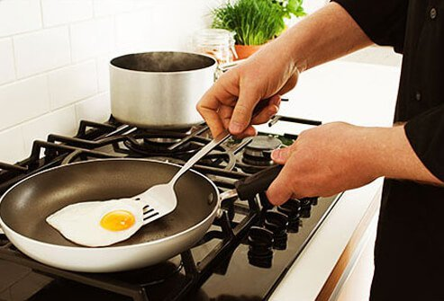 Photo of a person frying an egg sunny side up.