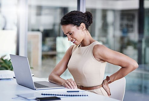 Does sitting all day at work cause back pain?