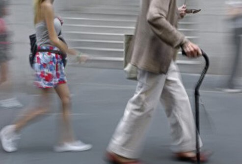 A man stabilizes himself with a walking cane.