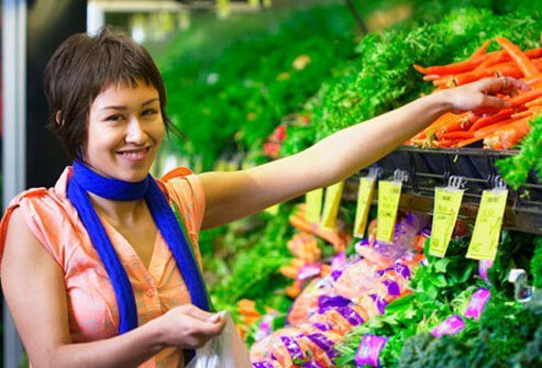 A woman picks out produce from the grocery store.