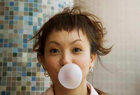 A woman blows a bubble with her chewing gum.