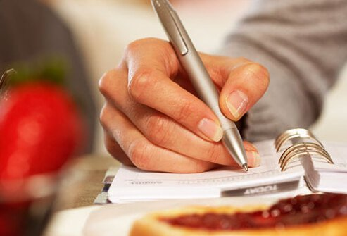 A woman writes inside a food diary.
