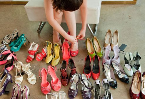 A woman tries on many different shoes.