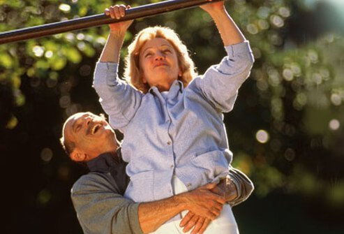 An elderly man helps his partner do a pull-up exercise.