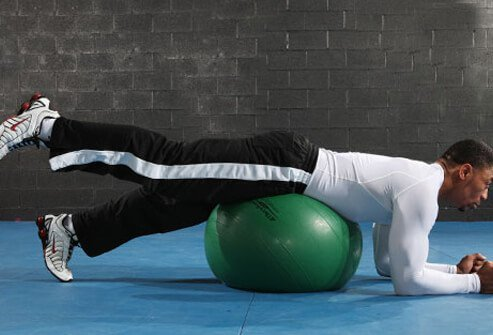 A man doing a leg lift on exercise ball.