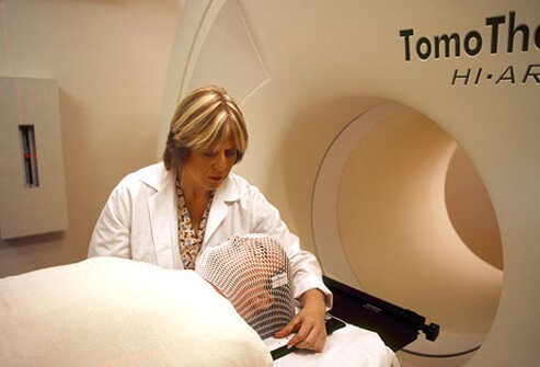 A radiation therapist prepares a patient for radiation treatment.