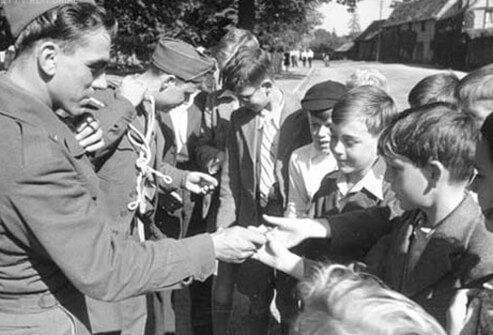 Soldiers hand out chocolate to French children during WWII.