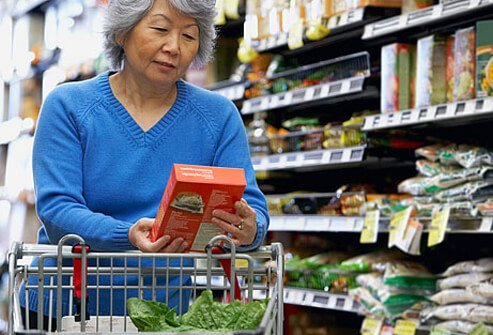 A woman looking at a nutrition label while grocery shopping.