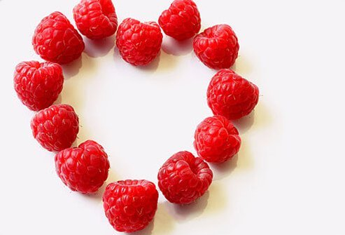 Red raspberries arranged in the shape of a heart.