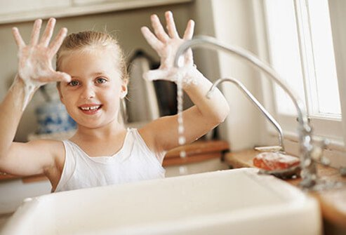 A little girl washing her hands to stop cold and flu virus.