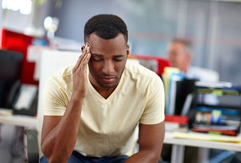A man with a headache suffering from cold and flu symptoms.