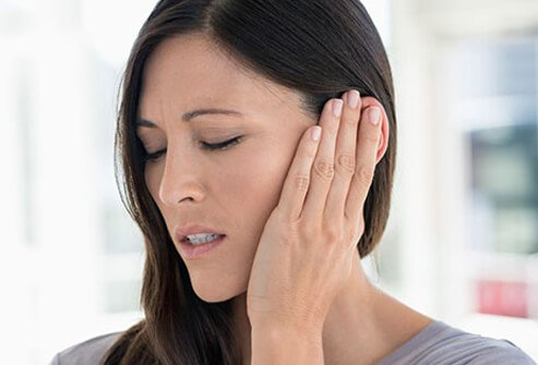 A woman is in pain suffering from an earache, a symptom of a cold and the flu.