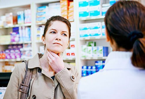 A woman suffering from a sore throat, a symptom of a cold and the flu.