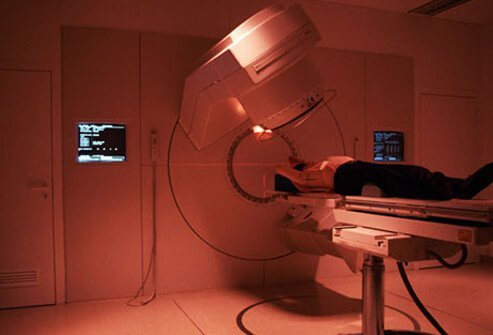 A man under a scanner being treated with radiation for colon cancer.