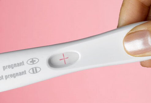 A woman's hand holding a positive pregnancy test.