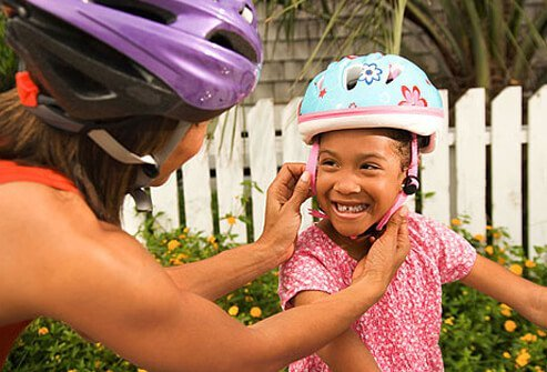 Photo of mother securing a helmet on her child.