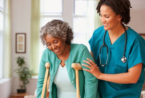 A doctor helps an injured senior woman on crutches.