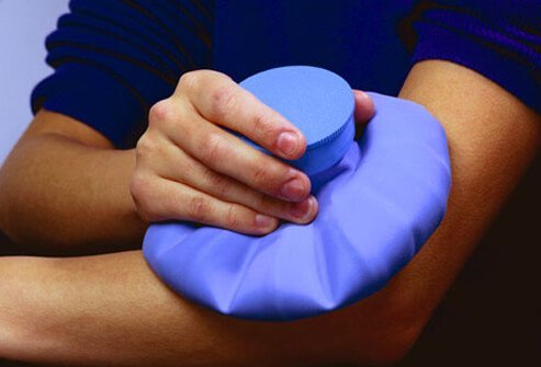 A man applies an ice pack to an injury on his arm.
