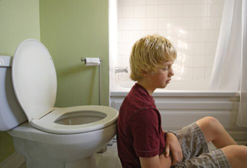 A teenage boy feeling ill after vomiting.