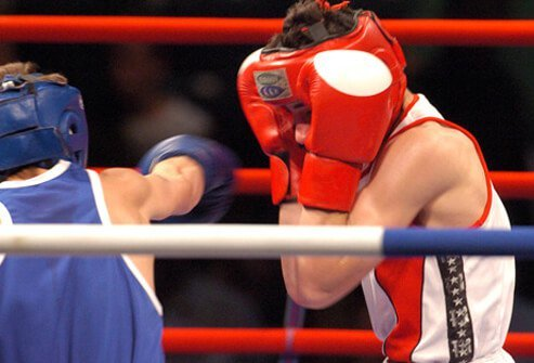 Boxers throwing punches during a boxing match, one of the causes of dementia pugilistica.