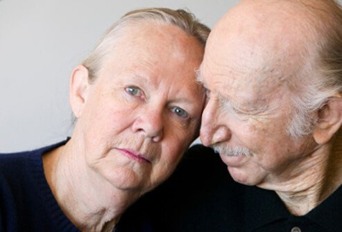 An elderly woman suffering from Alzheimer's disease is comforted by her husband.