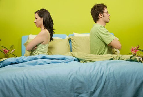 Photo of angry couple back to back in bed.
